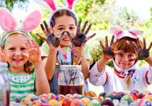Imagem ilustrativa de crianças vestidas de coelho da Páscoa e engajadas no tema de Páscoa, pintando com os dedos.